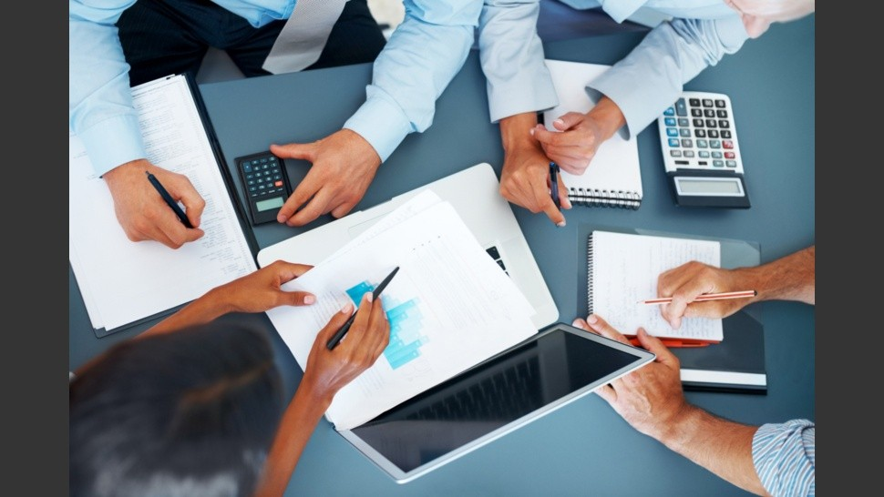 Accounting - Businesspeople working on charts and graphs - Cropped image of hands of businesspeople working together on business project at office - Consulting - J